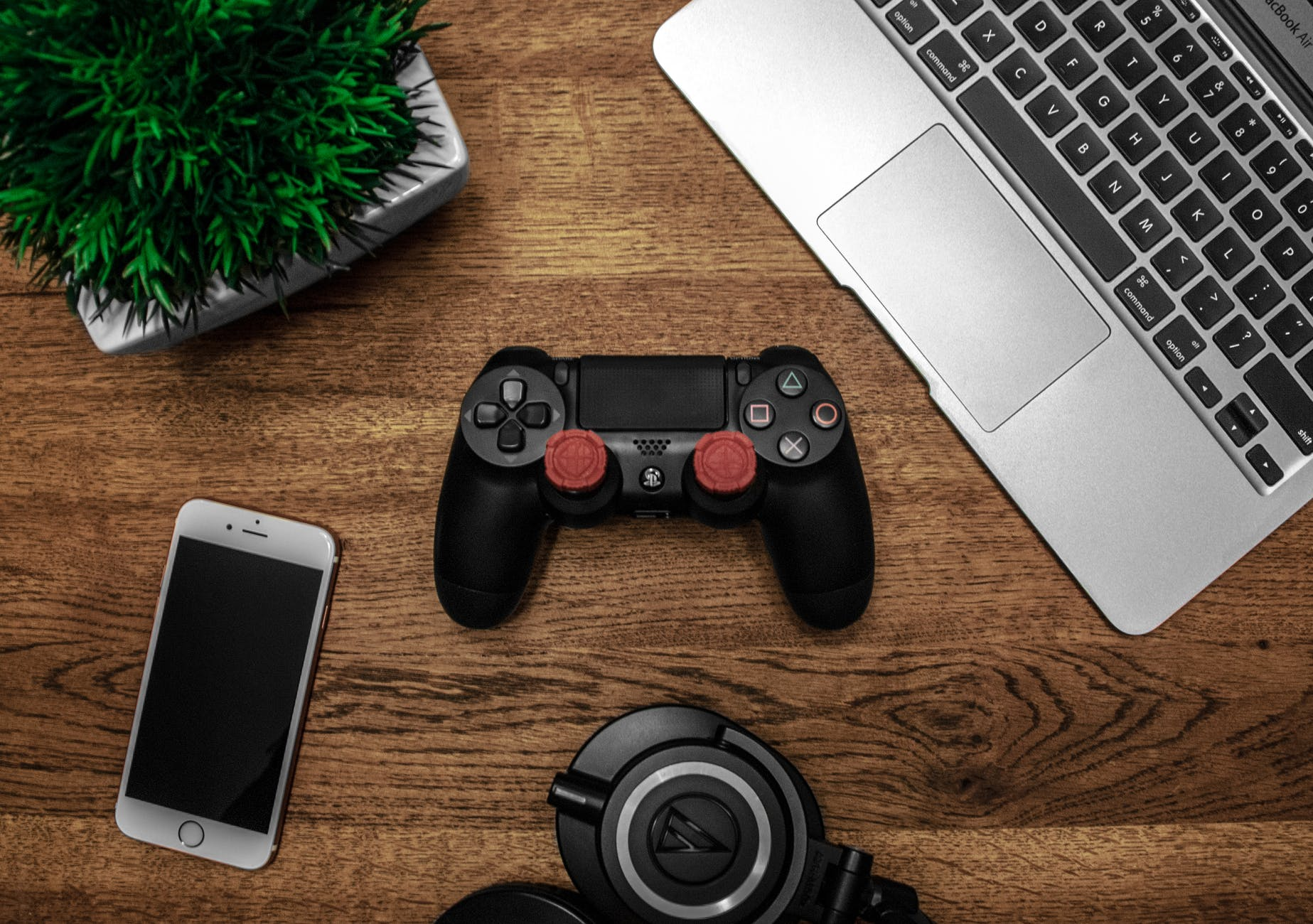 silver macbook beside black sony ps4 dualshock 4 silver iphone 6 and round black keychain on brown wooden table - Reach Out